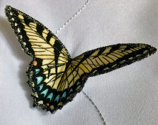 Closeup of yellow, embroidered butterfly